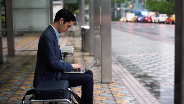 バスステーションでノートパソコンを使用して補聴器を持つビジネスマン - 公共交通機関点の映像素材/bロール