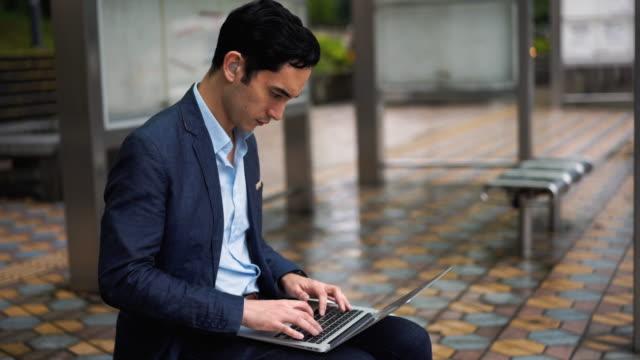 バスステーションでノートパソコンを使用して補聴器を持つビジネスマン - 道具類点の映像素材/bロール