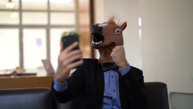 vídeos de stock e filmes b-roll de business man with horse mask taking a selfie at office - estupefação