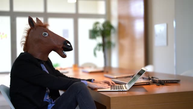 business man with horse mask working at office - piedi alzati video stock e b–roll