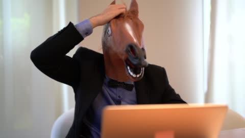 vidéos et rushes de homme d'affaires avec cheval masque travaillant au bureau - cheval