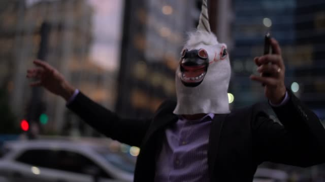 Business man with Unicorn Mask Celebrating