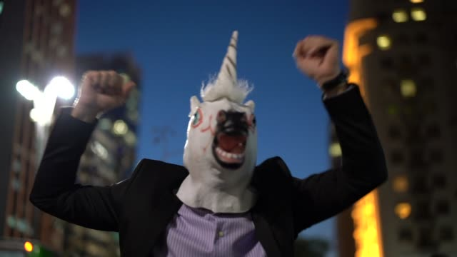 business man with unicorn mask celebrating - bizarre fashion stock videos and b-roll footage