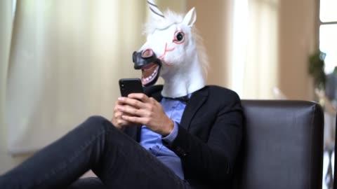 affärsman med unicorn mask använder mobil på kontor - individualitet bildbanksvideor och videomaterial från bakom kulisserna