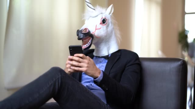 business man with unicorn mask using mobile at office - contrasts stock videos and b-roll footage