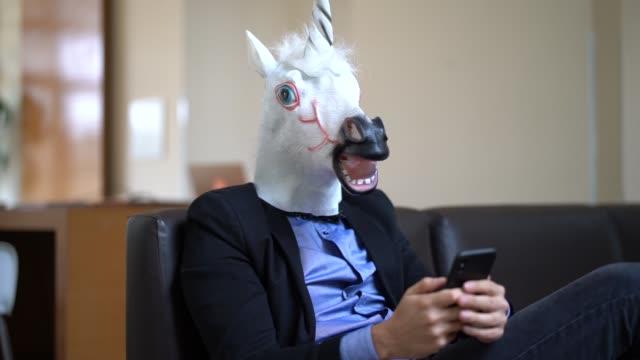 vídeos de stock, filmes e b-roll de homem de negócios com o unicórnio máscara usando mobile no escritório - criatividade