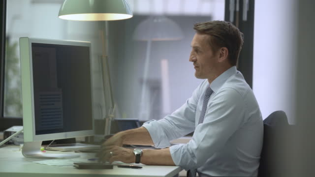 Business man working at computer then cheering