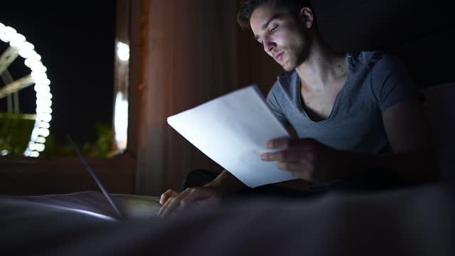 vídeos de stock, filmes e b-roll de homem de negócios trabalhando no final da noite na cama - excesso de trabalho
