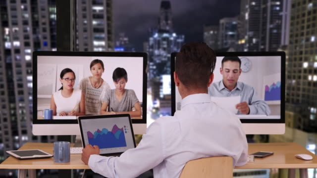 business man working late at night to have international video conference with diverse group of professional associates - voip stock videos & royalty-free footage