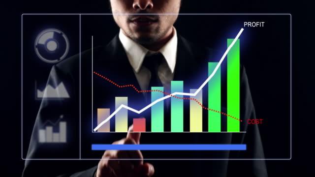 vidéos et rushes de homme d'affaires travaillant sur la technologie futuriste d'écran tactile avec le graphique financier de croissance - diagramme en bâtons