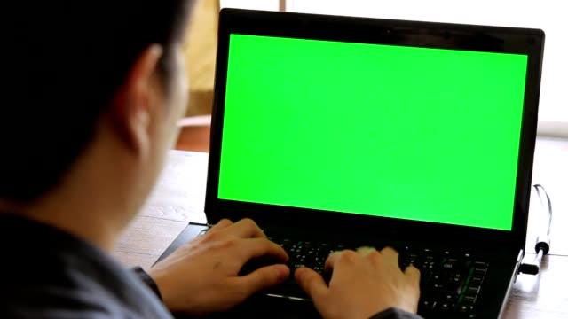 geschäftsmann arbeitet auf laptop-computer mit grünem bildschirm im büro - indoor-szene - über die schulter stock-videos und b-roll-filmmaterial