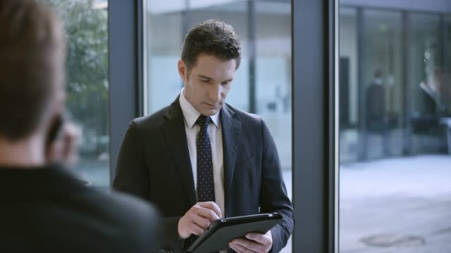 Business man working on tablet in the hallway