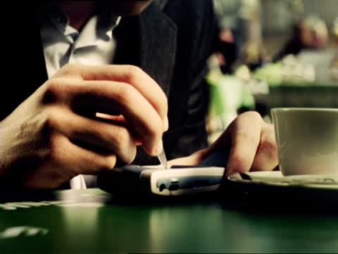 vídeos de stock, filmes e b-roll de cu, business man writing on mobile phone in cafe, ljubljana, slovenia - enfoque de objeto sobre a mesa