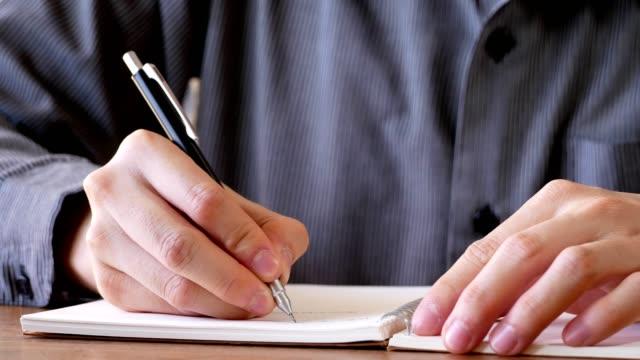 vídeos y material grabado en eventos de stock de hombre de negocios de la escritura sobre papel de cuaderno - instrumento de escribir con tinta