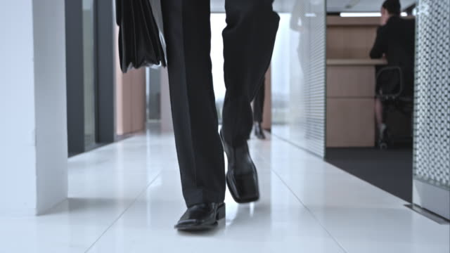 slo mo ds business mans shoes walking down hallway - walking stock videos & royalty-free footage