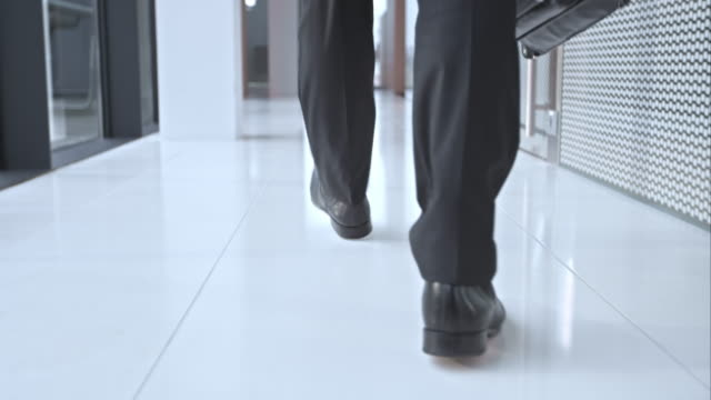 slo mo ds business mans shoes walking in hallway - human leg stock videos & royalty-free footage