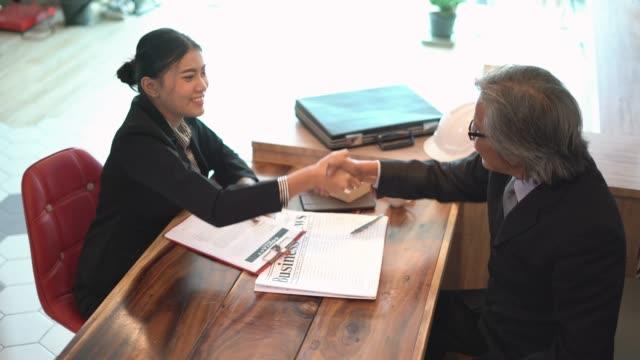 vidéos et rushes de réunion d'affaires et signe un contrat avec serrer la main au café-restaurant. - avocat juriste