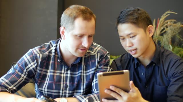 vídeos y material grabado en eventos de stock de reunión en el café usando la tableta - business talk frase corta