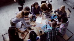 Business meeting at modern office. Top view of multiracial group of people working near the table together. Slow mo