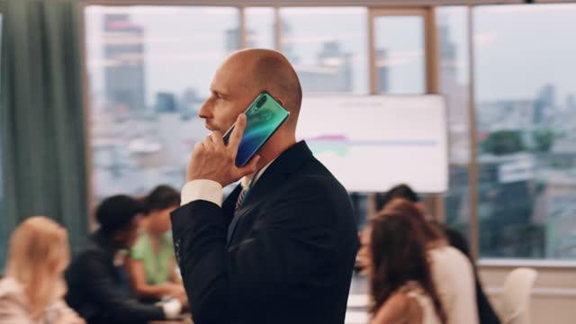 vídeos de stock, filmes e b-roll de reunião de negócios. empresário fazendo chamada de negócios. andando pela sala de embarque - vestuário de trabalho formal