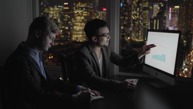 vidéos et rushes de business meeting in high rise city office at night. two young entrepreneurs - tenue d'affaires formelle