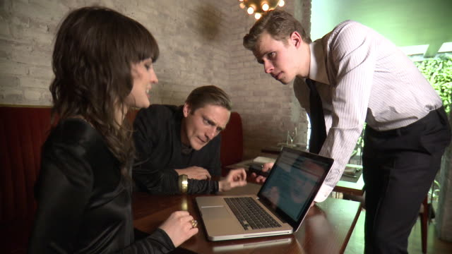 ms business men and woman discussing over laptop in restaurant, new york city, new york, usa - female with group of males stock videos and b-roll footage