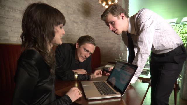 vídeos de stock e filmes b-roll de ms business men and woman discussing over laptop in restaurant, new york city, new york, usa - fotografia de três quartos