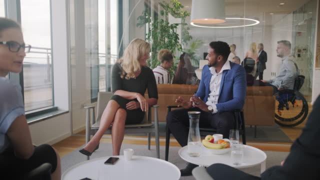 企業ロビーで話し合い、握手するビジネス男女 - ロビー点の映像素材/bロール