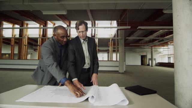 MS DS Business men discussing blueprint, Squamish, British Columbia, Canada