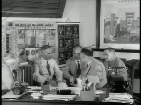 Business men in office talking MS Two men talking 'Air Raid Warden' poster BG MS Man looking at map plans Hong Kong WWII World War II