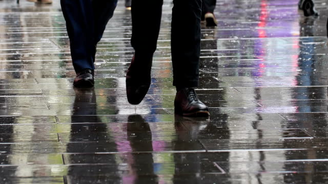 business men walking in city rain. lower body, legs and feet. - pioggia video stock e b–roll