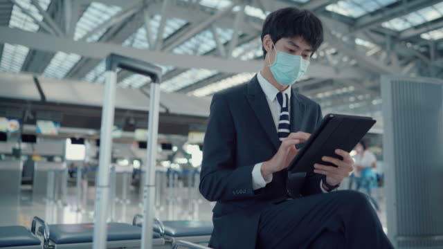 business men wear massages to protect against viruses while in the airport. - full suit stock videos & royalty-free footage