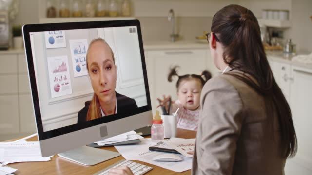 vídeos de stock e filmes b-roll de business mother having video call with colleague - domestic kitchen
