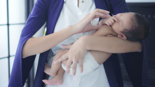 business mother holding sleeping baby boy in her arms - dondolarsi video stock e b–roll
