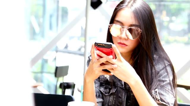 Geschäftlich unterwegs: schöne Mädchen, die mit ihrem Mobiltelefon im Café.