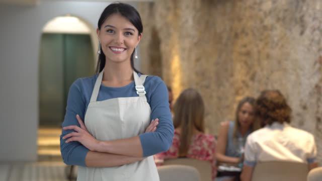 business owner bei ihrem restaurant mit blick in die kamera lächeln - gastwirt stock-videos und b-roll-filmmaterial