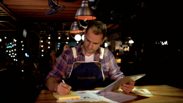 business owner at his restaurant doing the books using a tablet computer - small business stock videos & royalty-free footage