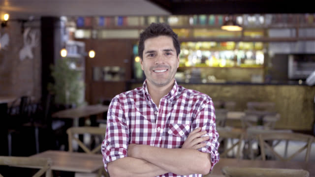 Business owner at his restaurant smiling at the camera