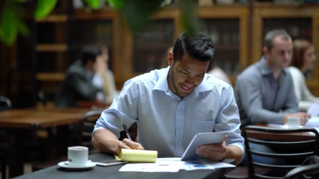 business owner checking the profits of the restaurant using a digital tablet and a notepad to take notes looking very happy - making money stock videos & royalty-free footage