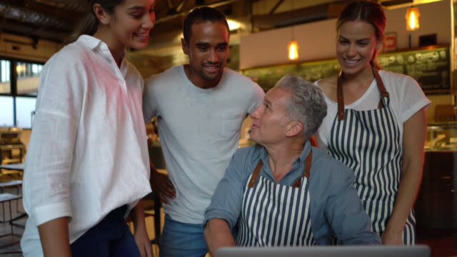 business owner of a bakery going over some information with his team while they are all looking at laptop smiling - food and drink industry stock videos & royalty-free footage