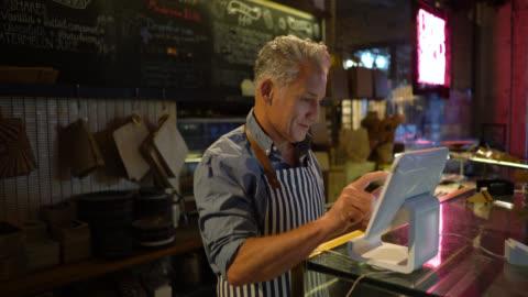 vídeos y material grabado en eventos de stock de dueño de negocio de una panadería que registra un pedido en sistema mirando muy feliz - gerente