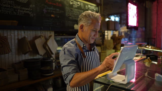 business owner of a bakery registering an order on system looking very happy - business stock videos & royalty-free footage