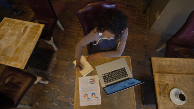 Business owner of a bar writing on a notepad using a laptop and documents