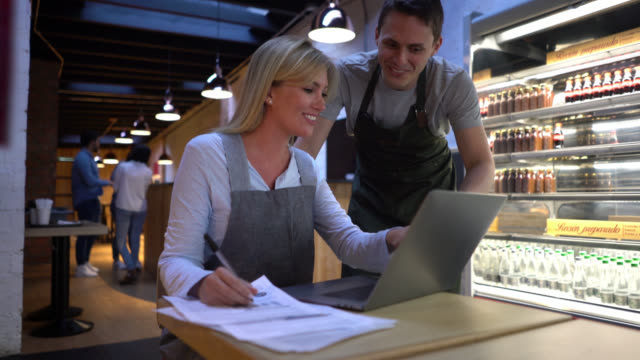 business owner of a coffee shop talking to male administrator while both are looking at the laptop's screen smiling - owner stock videos and b-roll footage