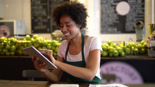 Business owner of a juice bar doing the books using a tablet and taking notes on a notepad looking very happy