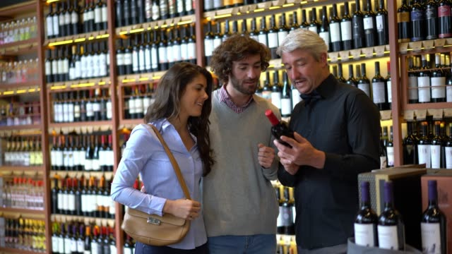 Business owner of a winery suggesting a good wine to a young loving couple all talking and smiling