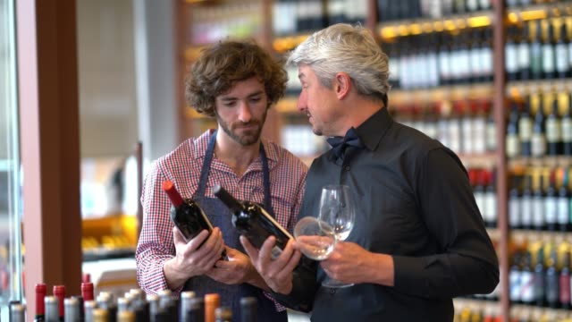 Business owner of a winery teaching the young salesman about wine and he asks questions while each is holding a bottle and wine glasses