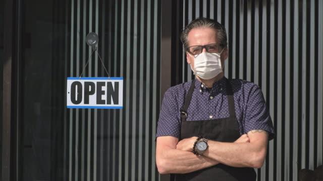 stockvideo's en b-roll-footage met bedrijfseigenaar die na quarantaine opent - bord open
