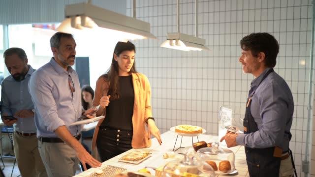 vidéos et rushes de propriétaire d'entreprise servant la nourriture faite maison aux clients à la cafétéria - file d'attente