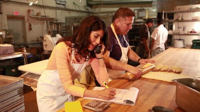 vídeos y material grabado en eventos de stock de ms business owner talking on phone and working in bakery / sante fe, new mexico, usa - teléfono sin cable